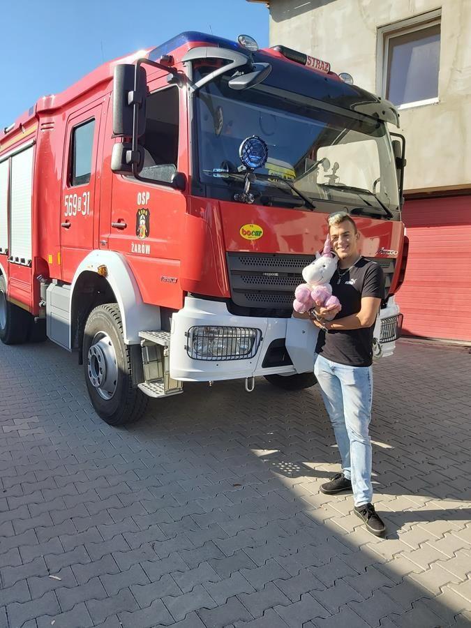 Stojący przed wozem strażackim Arkadiusz Mazur - inicjator akcji - trzymający pluszaka