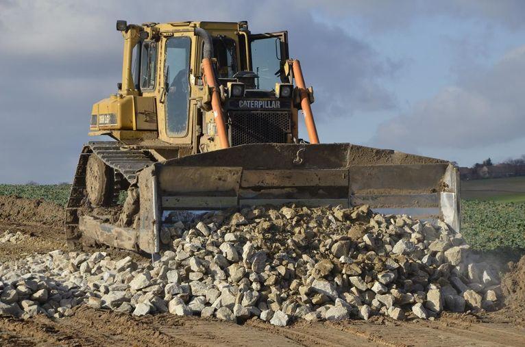 Koparka zbierająca kamienie na drodze w Pożarzysku
