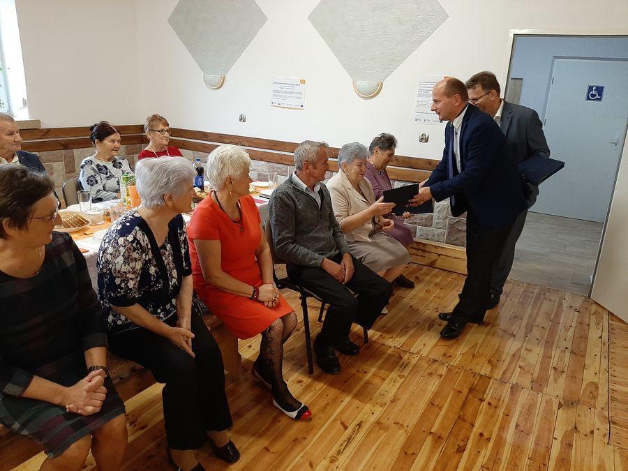 Zdjęcie przedstawia Burmistrza Pana Mirosława Gazdę oraz zastępcę  Pana Józefa Paćkowskiego wręczających list gratulacyjny Seniorce. Pierwsza z lewej Radna Pani Bogumiła Iracka-Burek.