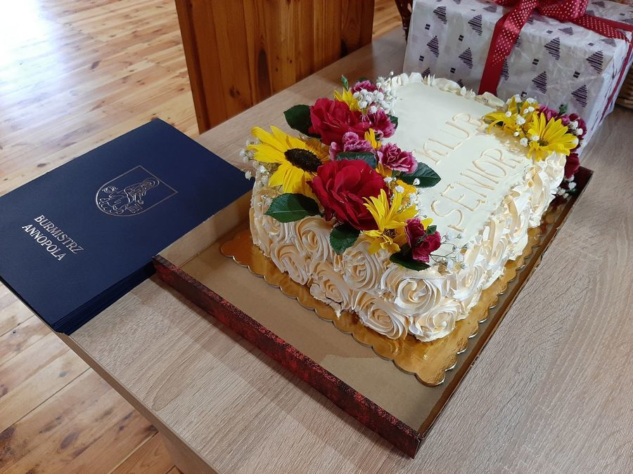 Zdjęcie przedstawia tort udekorowany żywymi kwiatami w kolorze żółtym, czerwonym i różowym z napisem Klub Senior+