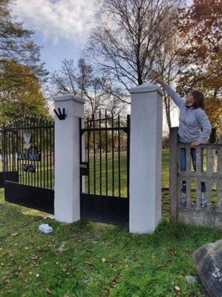 Brama wejściowa do Cmentarza wojennego przy ul. Balonnej w trakcie malowania elementów betonowych.