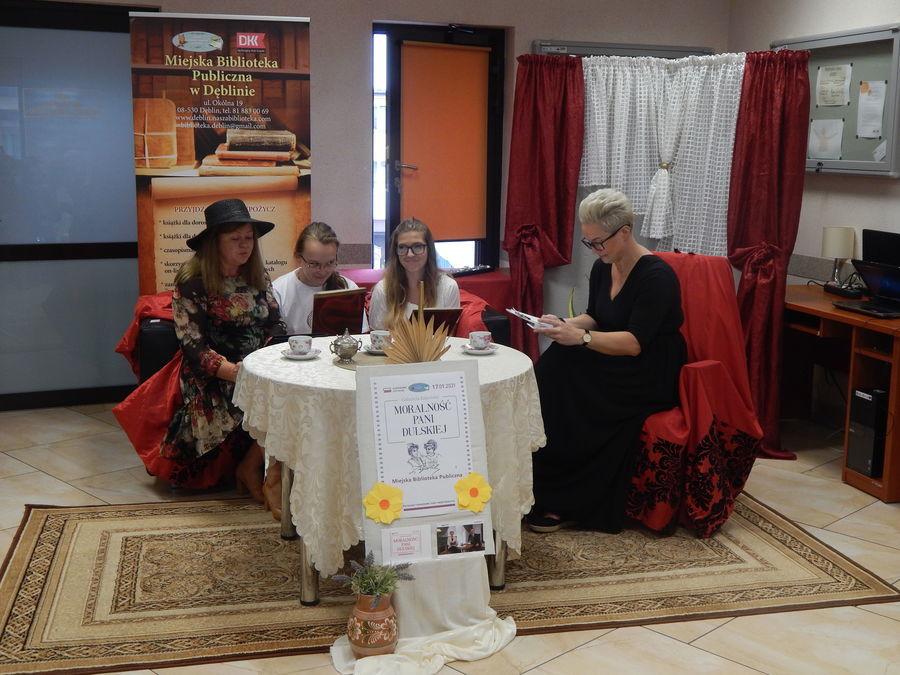 Cztery osoby siedzą przy stoliku na kanapie i czytają fragment Moralności pani Dulskiej.