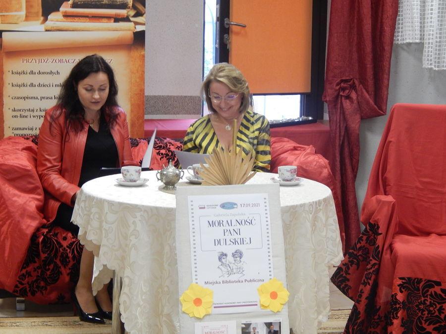 Dwie osoby siedzą przy stoliku na kanapie i czytają fragment Moralności pani Dulskiej.