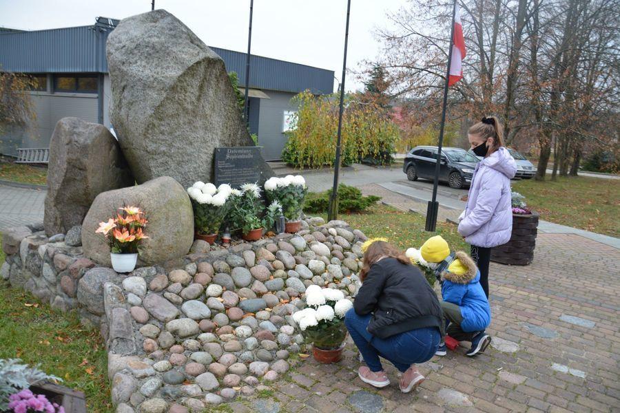 Ludzie w maseczkach przy pomniku