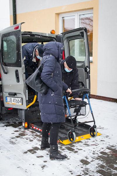 Zdjęcie przedstawia pomoc w transporcie do punktu szczepień osobie potrzebującej takiego wsparcia