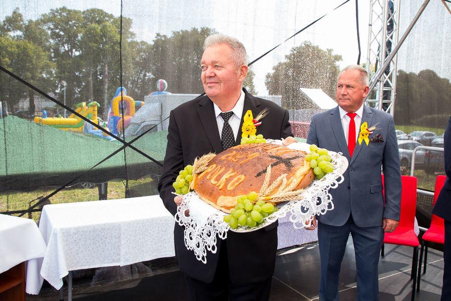 Na zdjęciu wójt prezentuje chleb dożynkowy uczestnikom wydarzenia