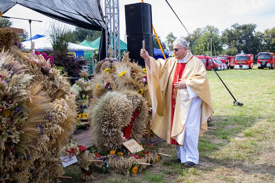 Na zdjęciu ksiądz kropi wieńce wodą święconą