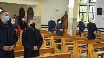 Osoby stojące w kościele podczas mszy