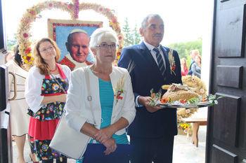 Starostowie dożynkowi niosący chleb