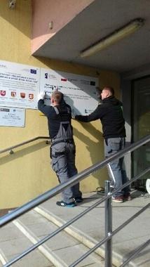 Dwie osoby przyczepiające tablice informacyjne