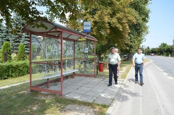 3 osoby przy przystanku autobusowym