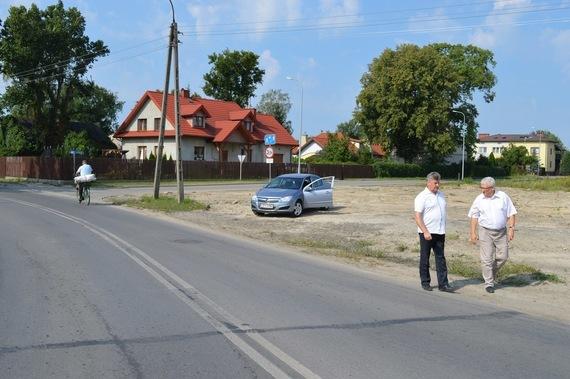 3 osoby przy ulicy na tle domków