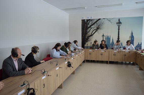 Grupa osób siedzących w słuchawkach