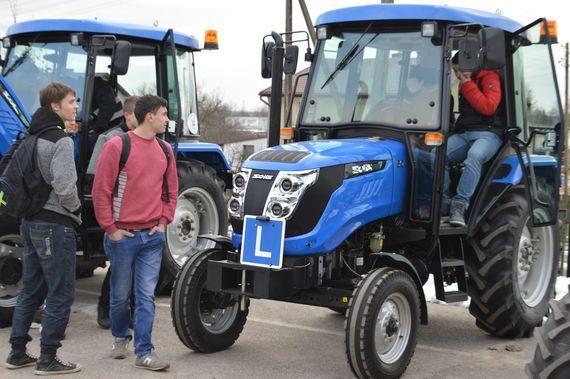 Grupa ludzi przy niebieskich ciągnikach
