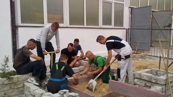 Grupa osób ucząca się kłaść kostkę