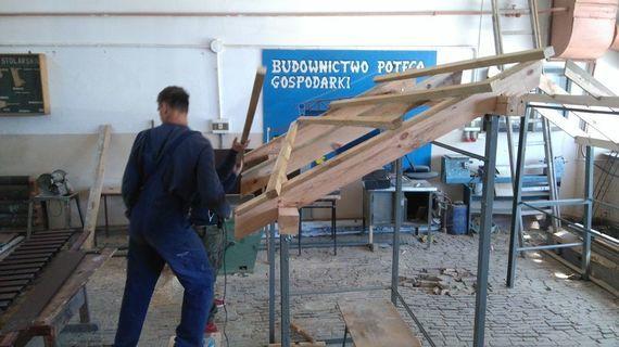 2 osoby tworzące konstrukcję z drewna
