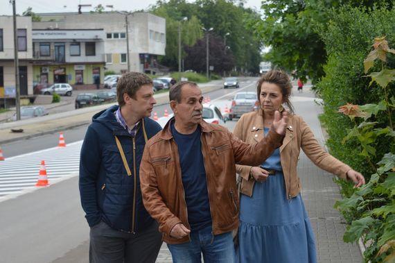 Grupa osób przy ulicy na tle samochodów