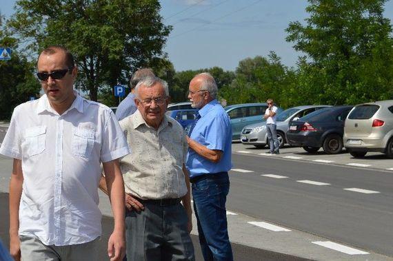 Grupa osób stojących na chodniku na tle samochodów