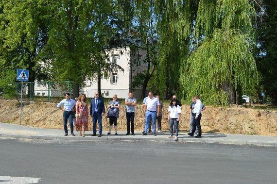 Grupa ludzi stojących na chodniku