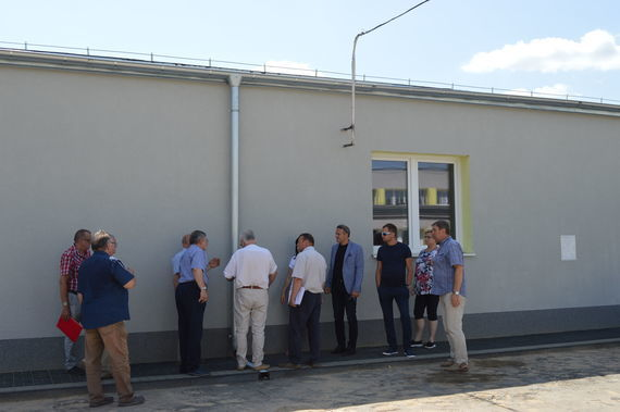 Grupa ludzi przy ścianie nowego budynku