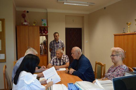 Grupa rozmawiających ludzi przy dokumentach