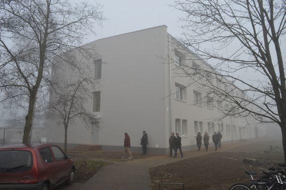 Grupa ludzi przy budynku internatu