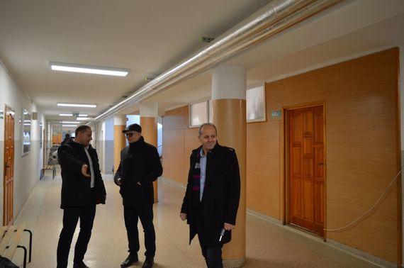 3 osoby rozmawiające na korytarzu