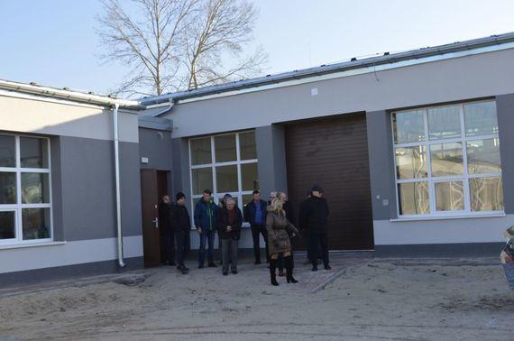 Grupa ludzi przy budynku szkolnym
