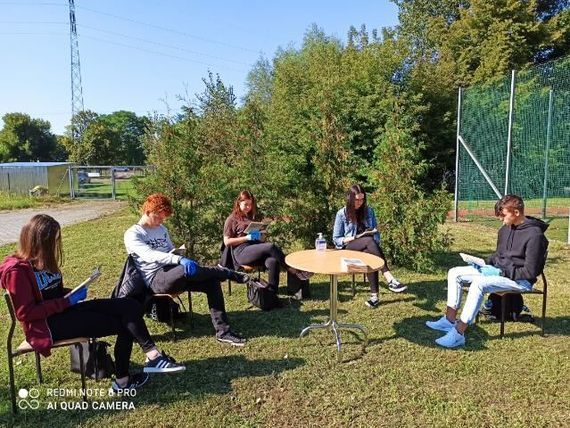 Grupa młodych ludzi na zewnątrz siedzących i czytających książki