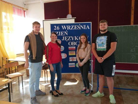 cztery osoby przy tablicy promującej  dzień języków obcych