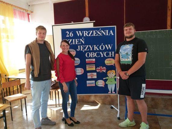 Trzy osoby przy tablicy promującej dzień języków obcych