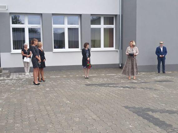 Rozpoczęcie Roku w Zespole Szkół Zawodowych zdjęcie osób przed budynkiem szkoły