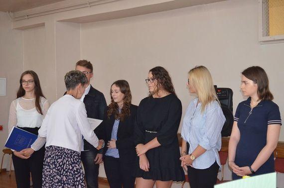 Zdjęcie grupy osób przyjmującyhc gratulację