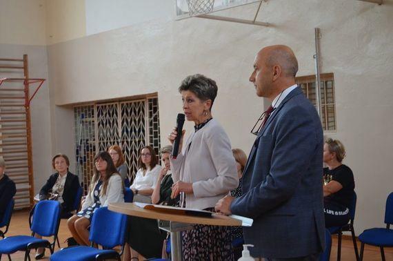 Rozpoczęcie roku - dwie osoby na zdjęciu jedna z mikrofonem w tle osoby siedzące