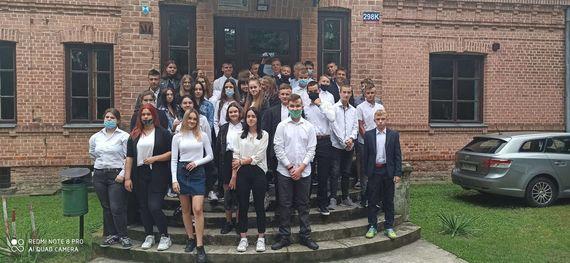 Grupa uczniów przed budynkiem rozpoczęcie roku szkolnego