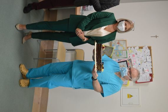 Dwie osoby stoją na zdjęciu z tortem