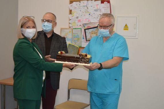 Trzy osoby stoją na zdjęciu z tortem