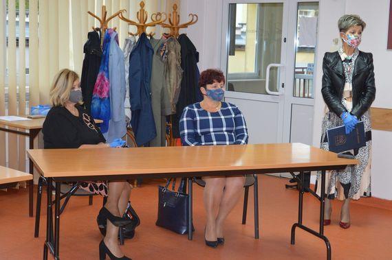 Dwie kobiety siedzące i jedna stojąca