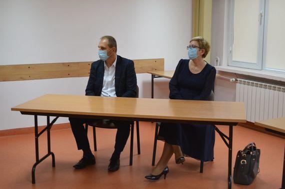 Dwie osoby siedzące za stołami
