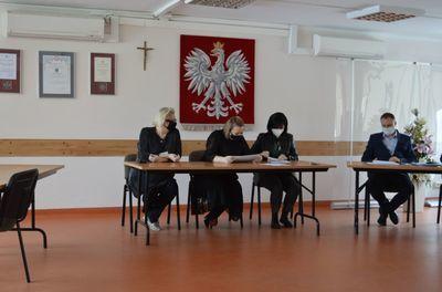 Osoby siedzące przy biurkach podczas otwarcia ofert