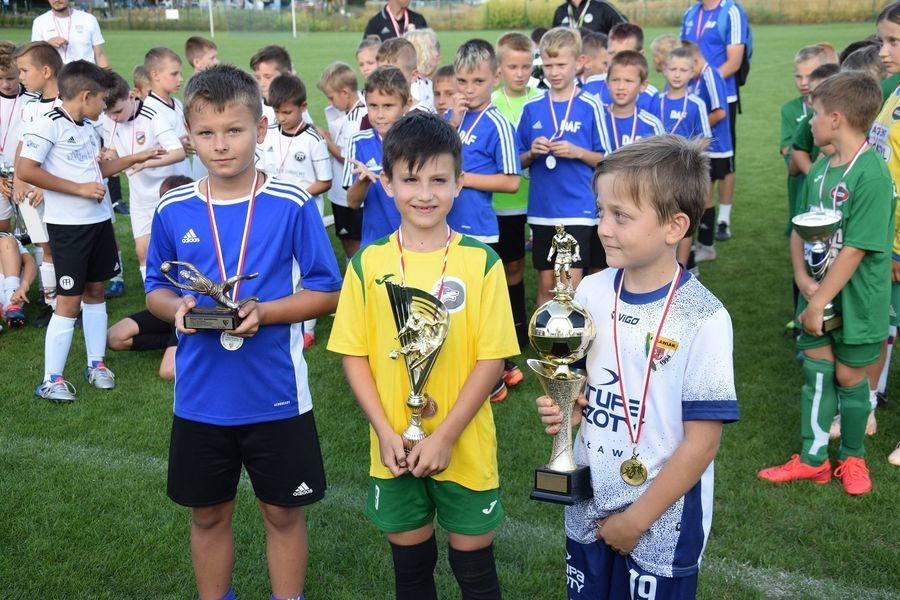 Piłkarze z medalem i pucharami, w tle pozostali zawodnicy
