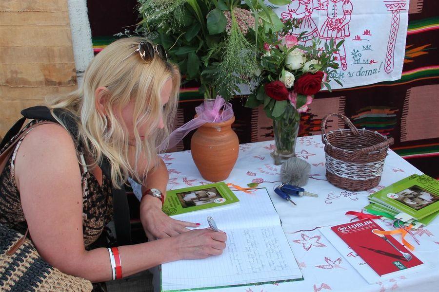Redaktor Radia Impuls J. Czajkowska w trakcie wpisu do księgi pamiątkowej