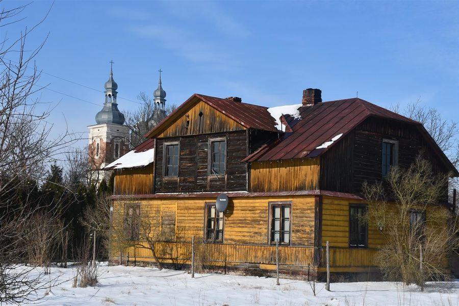 Stary dom w Gołębiu, w tle wieże kościelne