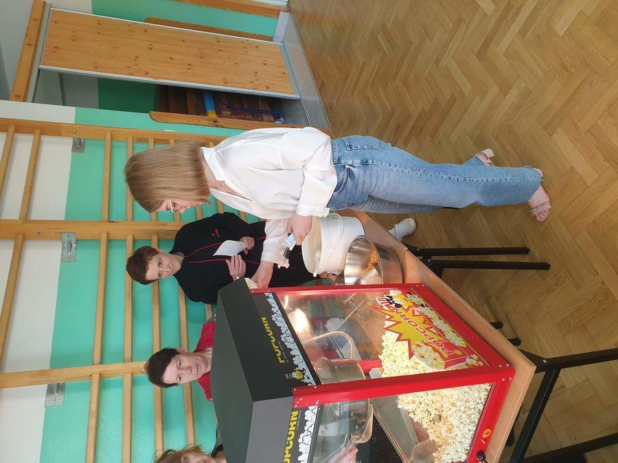 uczennica odbiera porcję popcornu