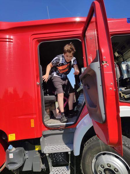 Uczeń wysiada z wozu strażackiego