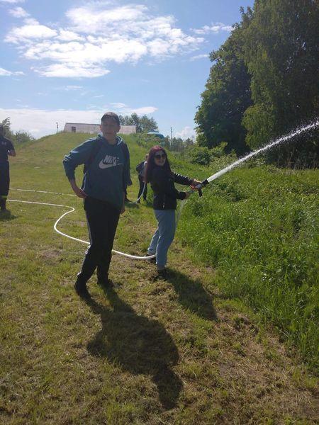 Uczennica polewa trawę wodą z węża strażackiego
