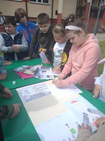 Uczniowie wykonują plakat o patronie szkoły