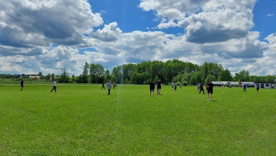 Uczniowie grają na boisku trawiastym do piłki nożnej