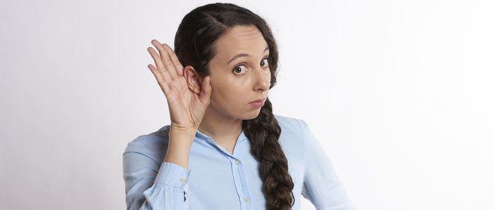 Kobieta z ręką przy uchu- nasłuchiwanie