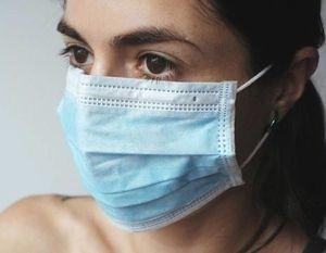 Grafika przedstawiająca kobietę w maseczce ochronnej